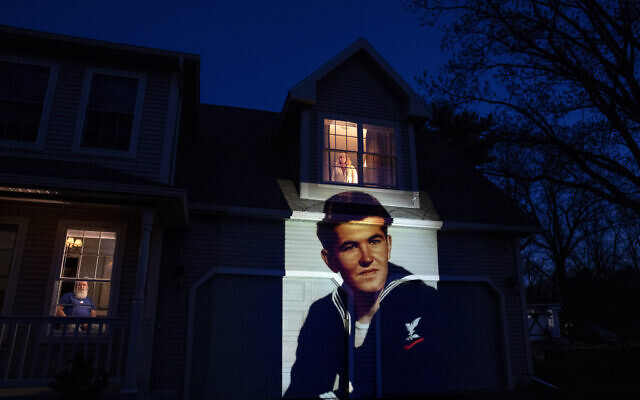 An image of veteran Stephen Kulig is projected onto the home of his daughter, Elizabeth DeForest, as she looks out the window of a spare bedroom as her husband, Kevin, sits downstairs in Chicopee, Mass., Sunday, May 3, 2020. Kulig, a US Navy veteran and resident of the Soldier's Home in Holyoke, Mass., died from the COVID-19 virus at the age of 92. After saying goodbye to her father for the last time in person, Elizabeth slept in the spare bedroom upstairs for two weeks as a precaution against possibly infecting her husband. Seeking to capture moments of private mourning at a time of global isolation, the photographer used a projector to cast large images of veterans on to the homes as their loved ones are struggling to honor them during a lockdown that has sidelined many funeral traditions. (AP/David Goldman)
