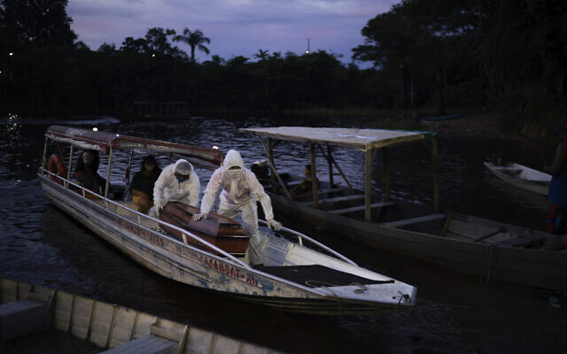 SOS Funeral workers transport by boat the coffin containing the body of a suspected COVID-19 victim that died in a river-side community near Manaus, Brazil on May 14, 2020. The victim, an 86-year-old woman, lived by the Negro river, the largest tributary to the Amazon river. (AP/Felipe Dana)