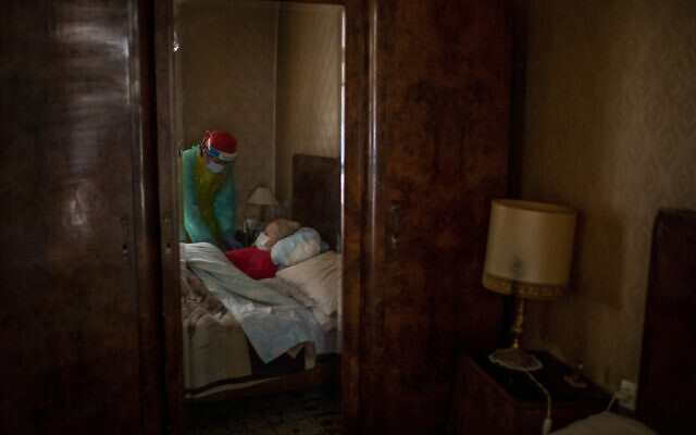 Josefa Ribas, 86, who is bedridden and suffers from dementia, is attended to by nurse Laura Valdes during a home care visit in Barcelona, Spain, April 7, 2020. Ribas' husband, Jose Marcos, fears what will happen if the virus enters their home and infects them. 'I survived the post-war period (of mass hunger). I hope I survive this pandemic,' he said. (AP/Emilio Morenatti)