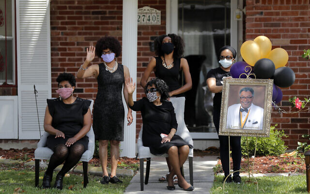 The family of Larry Hammond wave as a line of cars with friends and family, who could not attend his funeral because of limits of gatherings of more than 10 people, due to the coronavirus pandemic, pass by their home, in New Orleans, April 22, 2020. (AP/Gerald Herbert)