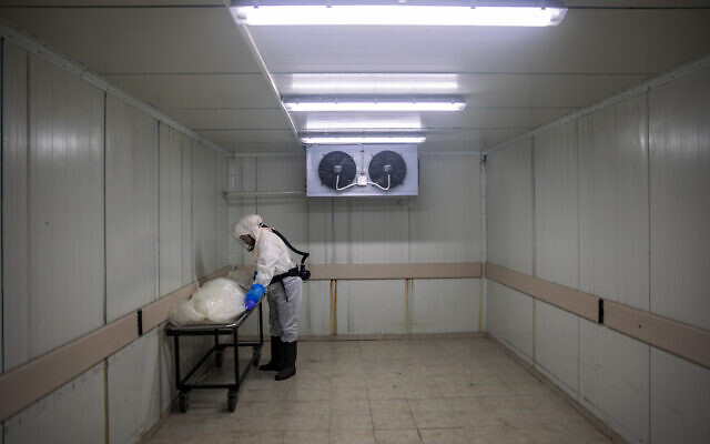 A worker from Hevra Kadisha, Israel's official Jewish burial society, prepares a body before a funeral procession at a special morgue for COVID-19 victims in Holon, September 23, 2020. (AP/Oded Balilty)