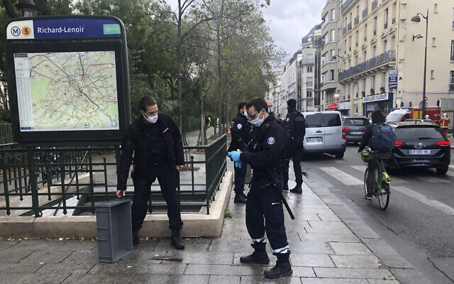 Police officers stand by a knife, seen on the ground, in Paris, September 25, 2020. (Soufian Fezzani Via AP)