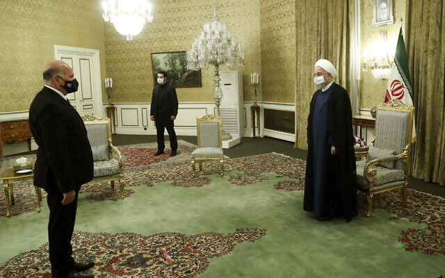 In this photo released by the official website of the office of the Iranian Presidency, President Hassan Rouhani, right, welcomes Iraqi Foreign Minister Fuad Hussein for their meeting, in Tehran, Iran, September 26, 2020. (Iranian Presidency Office via AP)