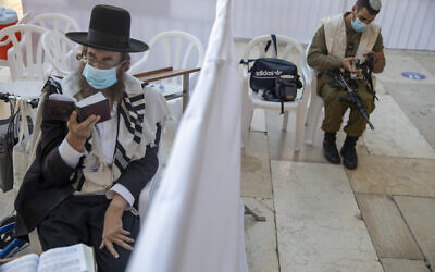 With a social distancing barrier, an ultra-Orthodox Jewish man and an Israeli soldier pray ahead of Yom Kippur at the Western Wall in Jerusalem's Old City, September 27, 2020. (AP Photo/Ariel Schalit)
