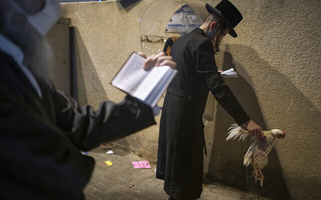 An ultra-Orthodox Jewish man holds a chicken as part of the Kaparot ritual, in Bnei Brak, September 27, 2020. (AP Photo/Oded Balilty)