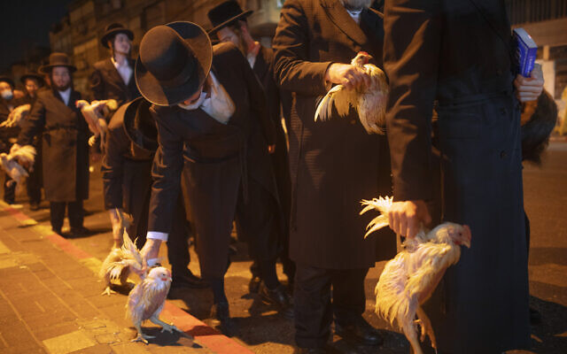 Ultra-Orthodox Jews hold chickens later to be slaughtered during the Kaparot ritual, in Bnei Brak, Israel, September 27, 2020. (AP Photo/Oded Balilty)