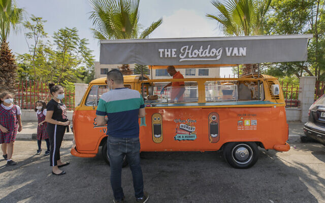 Emad Abdeljawwad sells grilled hot dogs and beverages out of a converted van in the West Bank city of Ramallah, Sept. 23, 2020. With dine-in restaurants mostly closed due to health restrictions, food trucks have allowed entrepreneurial palestinian businessmen to find a way to keep working. (AP/Nasser Nasser)
