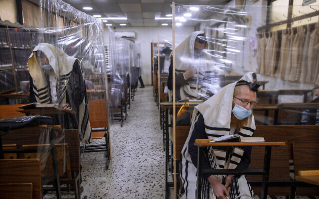 In this Monday, September 21, 2020 file photo, ultra-Orthodox Jews wear face masks during a morning prayer in a synagogue separated by plastic partitions, in Bnei Brak, Israel. (AP/Oded Balilty, File)