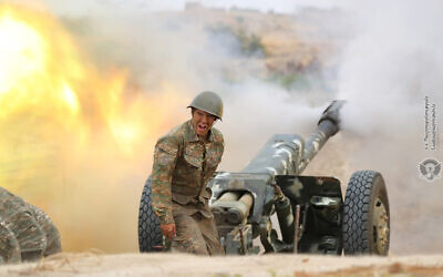 In this photo released by Ministry of Defense of Armenia on Tuesday, Sept. 29, 2020, an Armenian soldier fires an artillery piece during fighting with Azerbaijan's forces in the breakaway region of Nagorno-Karabakh. (Ministry of Defense of Armenia via AP)