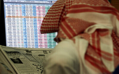 A Saudi man reads a newspaper while keeping an eye on a screen displaying stock market figures, at al Jazeera Capital Bank in Riyadh, Saudi Arabia, March 19, 2008. (Hasan Jamali/AP)