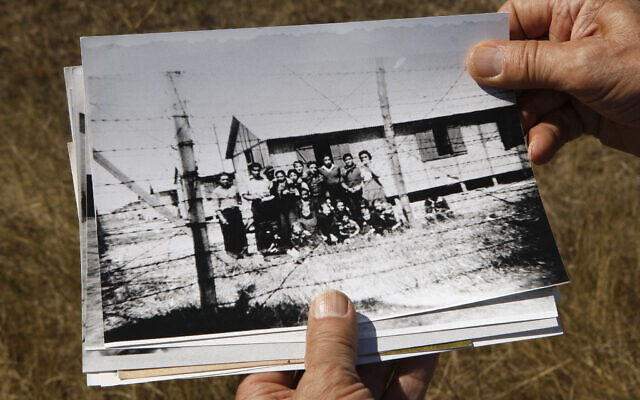Retired schoolteacher Jacques Sigot shows photos taken of unidentified inmates of a camp where thousands of French Gypsies were interned in the village of Montreuil-Bellay, in the Saumur wine region, during World War II,  Sept. 8, 2010 (AP Photo/Michel Euler)