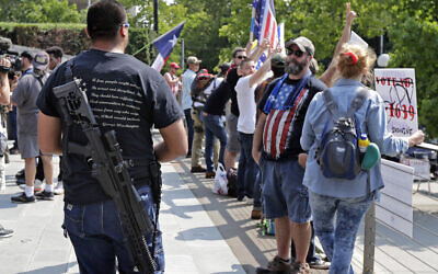 A man standing with members of Patriot Prayer and other groups supporting gun rights wears a gun during a rally, Aug. 18, 2018, at City Hall in Seattle. (AP Photo/Ted S. Warren)
