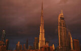 Sunlight reflects off the Burj Khalifa, the world's tallest building, during a rain shower in Dubai, United Arab Emirates, Monday, Nov. 26, 2018 (AP Photo/Jon Gambrell)