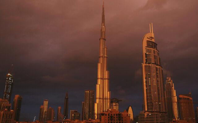 Sunlight reflects off the Burj Khalifa, the world's tallest building, during a rain shower in Dubai, United Arab Emirates, Monday, Nov. 26, 2018 (AP Photo/Jon Gambrell)