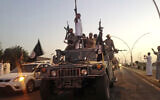 IS fighters parade in commandeered Iraqi security forces armored vehicles down a main road at the northern city of Mosul, Iraq, more than two weeks after taking over the country's second largest city, June 23, 2014. (AP Photo)