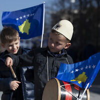 A boy plays on a drum decorated with Kosovo's flag to celebrate the 12th anniversary of the country's independence, in the capital Pristina, Monday, Feb. 17, 2020. (AP/Visar Kryeziu)