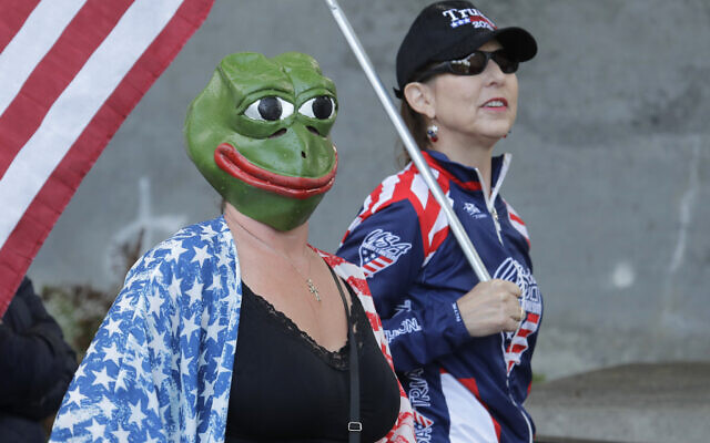 """A woman wears a mask of Pepe the Frog, a cartoon figure appropriated by far-right groups, as she stands next to a woman holding a US flag and a """"Trump 2020"""" hat, Thursday, May 14, 2020, during a protest rally at the Capitol in Olympia, Wash.  (AP Photo/Ted S. Warren)"""