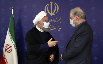In this photo released by the official website of the office of the Iranian Presidency, President Hassan Rouhani, left, talks with his Minister of Health and Medical Education Saeed Namaki during a meeting in Tehran, Iran, Saturday, July 4, 2020. (Iranian Presidency Office via AP)