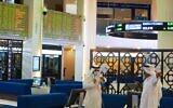 Two Emiratis wearing face masks due to the coronavirus pandemic talk on the floor of the Dubai Financial Market in Dubai, United Arab Emirates, July 7, 2020 (AP Photo/Jon Gambrell)