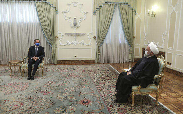 In this photo released by the official website of the office of the Iranian Presidency, President Hassan Rouhani, right, meets Director General of International Atomic Energy Agency, IAEA, Rafael Mariano Grossi at the presidency office in Tehran, Iran, Wednesday, Aug. 26, 2020. (Iranian Presidency Office via AP)