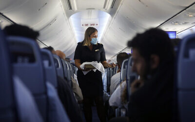 A flight attendant hands out chocolates with a greeting card to passengers on an El Al plane from Israel en route to Abu Dhabi, United Arab Emirates, Monday, Aug. 31, 2020. (Nir Elias/Pool Photo via AP)