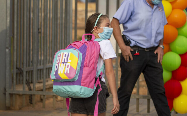 An elementary school student wearing a mask amid the coronavirus pandemic makes her way to class on the first day of school in Kfar Yona, Sept. 1, 2020. (AP Photo/Ariel Schalit)