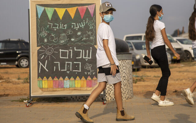 Elementary school students wearing masks amid the coronavirus pandemic walk past a signs reads 'Happy New Year, Hello First Grade' on the first day of school in Kfar Yona, Sept. 1, 2020. (AP Photo/Ariel Schalit)