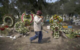 A grave digger walks in the COVID-19 section of the cemetery of San Lorenzo Tezonco Iztapalapa on the outskirts of Mexico City, Sept. 1, 2020. (AP Photo/Marco Ugarte)