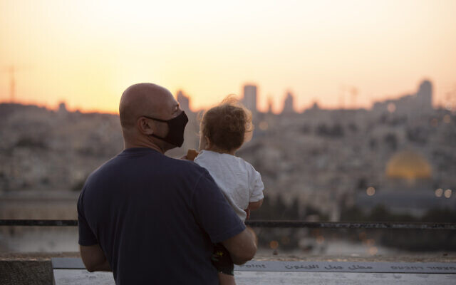 A man wearing a mask to curb the spread of the coronavirus holds a child on an overlook at the Mount of Olives as they watch the sun set behind the Dome of the Rock in Jerusalem, September 2, 2020. (AP Photo/Maya Alleruzzo)