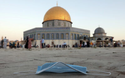 A protective face mask is left on the ground during the Eid al-Adha prayers, next to the Dome of the Rock at the Temple Mount compound in Jerusalem's Old City, July 31, 2020. (AP Photo/Mahmoud Illean, File)