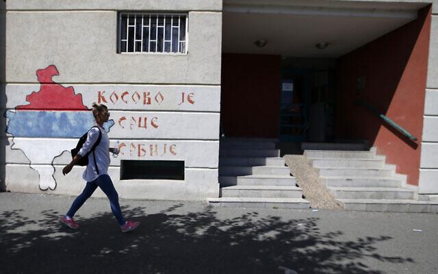 A girl walks past graffiti on a wall reading 'Kosovo is the heart of Serbia,' in Belgrade, Serbia, on Friday, September 4, 2020. (AP Photo/Darko Vojinovic)