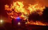 Flames lick above vehicles on Highway 162 as the Bear Fire burns in Oroville, California, on Sept. 9, 2020 (AP Photo/Noah Berger)