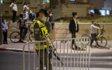 In this September 8, 2020, photo, an Israeli border policeman sets up a barrier as ultra-Orthodox Jews wearing face masks during the coronavirus pandemic wait to cross the street during an overnight curfew in Beit Shemesh (AP Photo/Ariel Schalit)