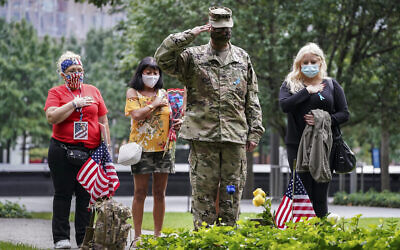US Army Sgt. Edwin Morales, center right, salutes after placing flowers for fallen FDNY firefighter Ruben D. Correa at the National September 11 Memorial and Museum, September 11, 2020, in New York. (AP Photo/John Minchillo)