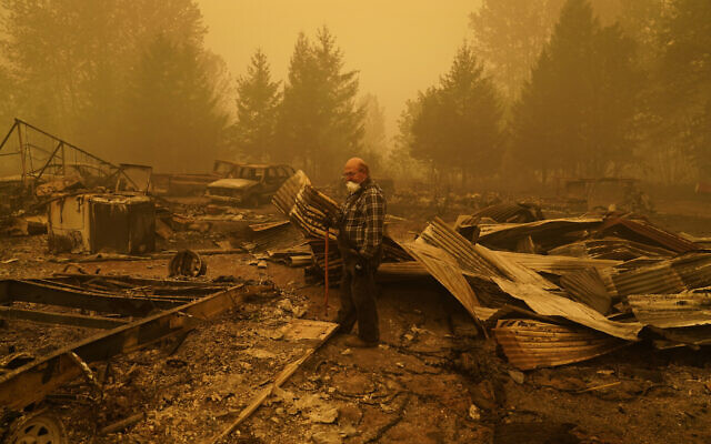 George Coble walks through what remains of a home on his property destroyed by a wildfire Saturday, Sept. 12, 2020, in Mill City, Ore. (AP/John Locher)