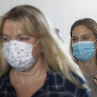 Israeli top model Bar Refaeli, right, and her mother, Tzipi Rafaieli wear face masks amid the coronavirus pandemic as they leave a courtroom in Tel Aviv, September 13, 2020 (AP Photo/Ariel Schalit, Pool)