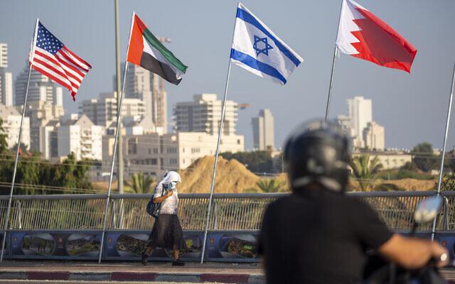 A woman wearing a face mask against the coronavirus pandemic walks past American, United Arab Emirates, Israel and Bahraini flags at the Peace Bridge in Netanya, Israel, Monday, Sept. 14, 2020.  (AP/Ariel Schalit)