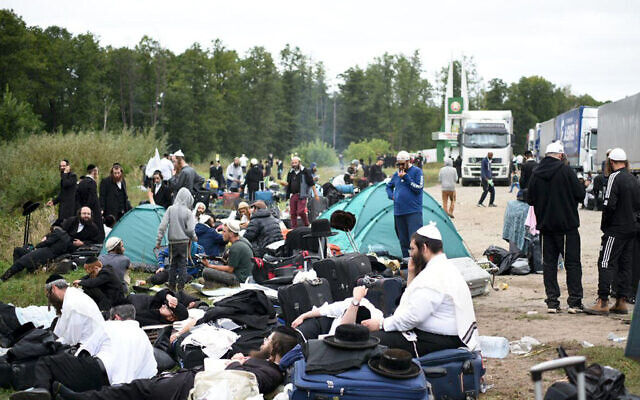Jewish pilgrims sit on the Belarus-Ukraine border, in Belarus, Tuesday, Sept. 15, 2020. About 700 Jewish pilgrims are stuck on Belarus' border due to coroavirus restrictions that bar them from entering Ukraine. (TUT.by via AP)