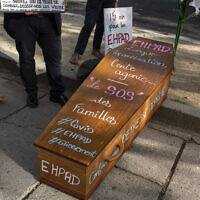 French protesters stand by a coffin for a protest, outside the French Health Ministry in support of medical workers of EHPAD (Housing Establishment for Dependant Elderly People), following the coronavirus outbreak, in Paris, France, September 16, 2020. (Rafael Yaghobzadeh/AP)