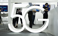 Visitors wearing mask to protect from the coronavirus walk past a 5G sign at the China Beijing International High Tech Expo in Beijing, China on September 17, 2020. (AP Photo/Ng Han Guan)