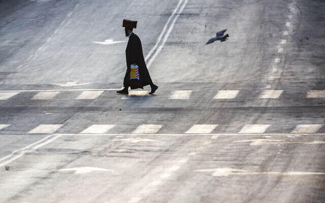 Anultra-Orthodox Jew crosses an empty street during the first day of the three-week lockdown in Bnei Brak, Israel, Friday, Sept. 18, 2020.  (AP Photo/Ariel Schalit)