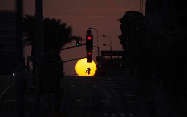 A person rides a bicycle on an empty street as the sun sets on the first day of three-week lockdown in Tel Aviv, Israel, Friday, Sept. 18, 2020. (AP Photo/Ariel Schalit)