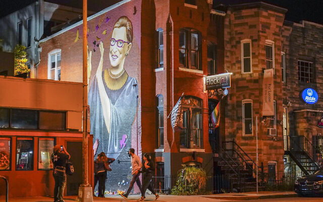 People gather under a mural of Supreme Court Justice Ruth Bader Ginsburg in the U Street neighborhood in Washington, Sept. 18, 2020, after the announcement that Ginsburg died of metastatic pancreatic cancer at age 87. (AP Photo/Pablo Martinez Monsivais)