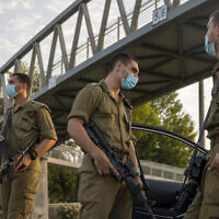 Israeli soldiers wear face masks at a police roadblock in Tel Aviv during the nationwide lockdown due to the coronavirus pandemic, Sept. 19, 2020 (AP Photo/Ariel Schalit)
