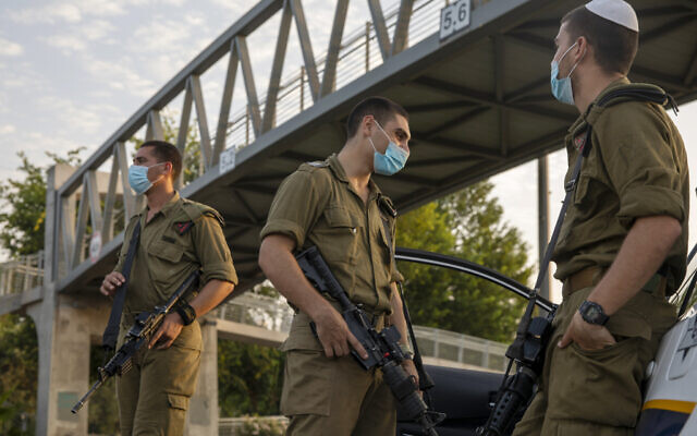 Israeli soldiers wear face masks at a police roadblock in Tel Aviv during the nationwide lockdown due to the coronavirus pandemic, Saturday, Sept. 19, 2020 (AP Photo/Ariel Schalit)
