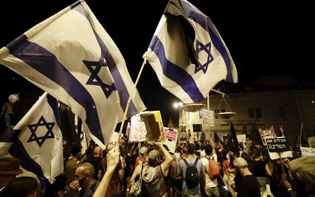 Anti-Netanyahu protesters wave flags, hold signs and chant slogans during a demonstration outside the Prime Minister's Residence in Jerusalem, September 20, 2020. (AP Photo/Sebastian Scheiner)