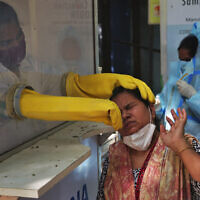 A health worker collects a nasal swab sample to test for COVID-19 in Hyderabad, India, Sept. 22, 2020  (AP Photo/Mahesh Kumar A.)