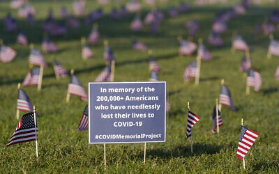 Activists from the COVID Memorial Project mark 200,000 lives lost in the US to COVID-19 after placing thousands of small American flags on the grounds of the National Mall in Washington, September 22, 2020. (J. Scott Applewhite/AP)