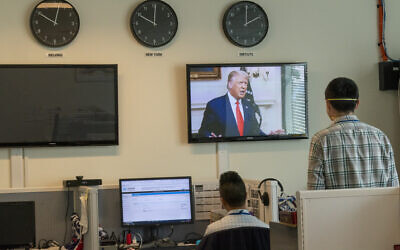 Reporters with the Xinhua Press Agency watch as US President Donald Trump is seen on a video screen remotely addressing the 75th session of the United Nations General Assembly on September 22, 2020, at UN headquarters. (AP/Mary Altaffer)