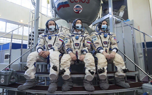 International Space Station (ISS) Expedition 64th crew members, from left, Russian cosmonauts Sergey Kud-Sverchkov, Sergey Ryzhikov and US astronaut Kathleen Rubins wearing face masks to protect against coronavirus pose during their final preflight practical examination in a mock-up of a Soyuz space craft at the Gagarin Cosmonaut Training Centre in Star City, outside Moscow, Russia, September 23, 2020. (Andrey Shelepin/Roscosmos Space Agency Press Service via AP)